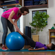 Female physiotherapist helping girl patient in performing stretching  exercise on exercise mat - PhotoDune Item for Sale