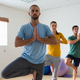 Free Download Instructor with students practicing tree pose in health club Nulled