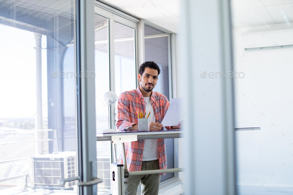 Smiling male executive holding document - Stock Photo - Images