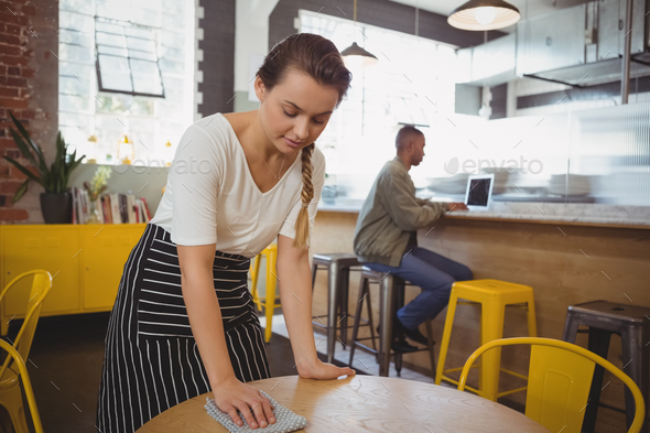 Waitress cleaning table - Stock Photo - Images