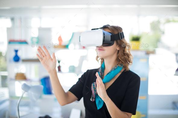 Female executive using virtual reality headset - Stock Photo - Images