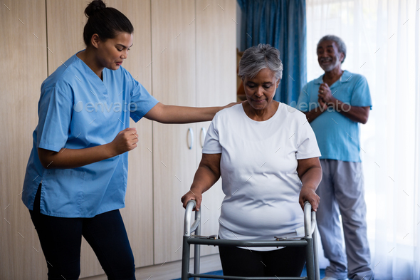 Nurse assisting senior woman in walking with walker - Stock Photo - Images
