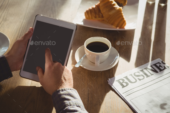 Cropped hands of businessman using tablet in cafe - Stock Photo - Images