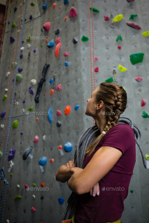 Athlete with rope looking up while standing by climbing wall in club - Stock Photo - Images