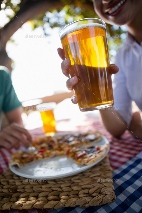 Cropped image of woman holding beer glass - Stock Photo - Images