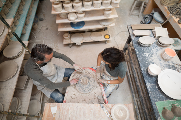 Overhead of male potter assisting female potter - Stock Photo - Images