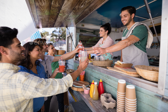 Waitress and waiter giving juice to customer at counter - Stock Photo - Images