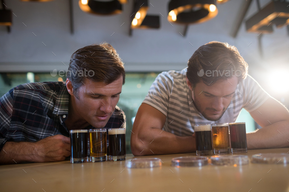 Male friends looking at beer glass at bar counter - Stock Photo - Images