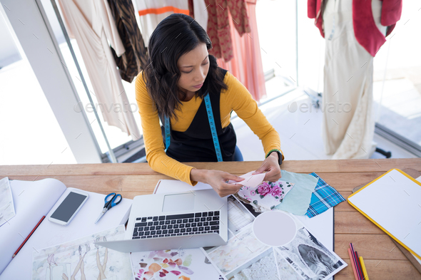 Female designer working on pieces of clothes - Stock Photo - Images