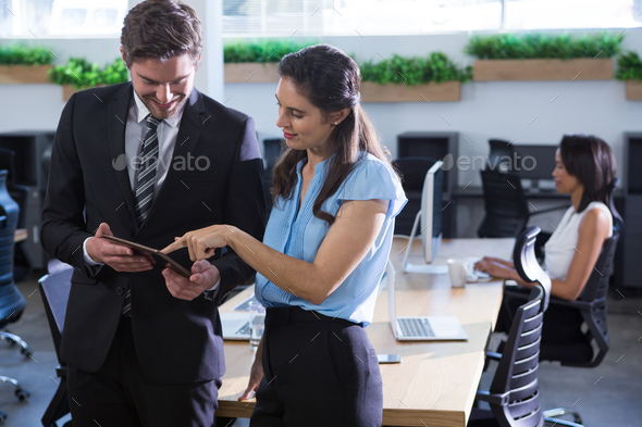 Executives discussing over tablet in background other executive working - Stock Photo - Images