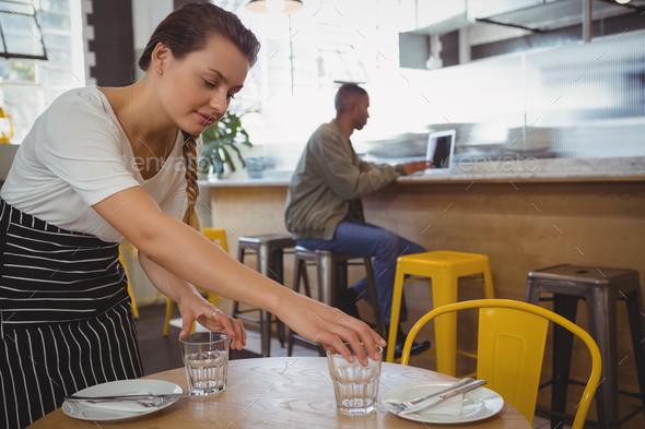 Waitress arranging glasses with businessman using laptop - Stock Photo - Images