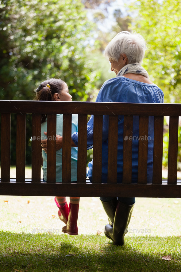Fabulous Rear View Of Grandmother And Granddaughter Sitting On Wooden Bench Ocoug Best Dining Table And Chair Ideas Images Ocougorg