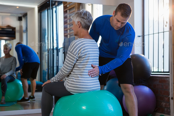 Physiotherapist assisting senior woman on exercise ball - Stock Photo - Images