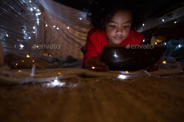 Girl using digital tablet in bedroom - Stock Photo - Images