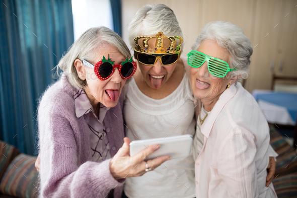 Senior women wearing novelty glasses making face while taking selfie - Stock Photo - Images