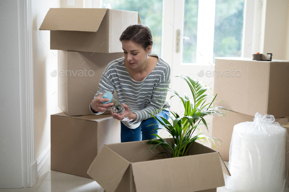 Woman opening cardboard boxes in living room - Stock Photo - Images