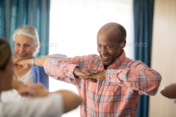 Smiling senior man standing with hands clasped with friends and female doctor - Stock Photo - Images