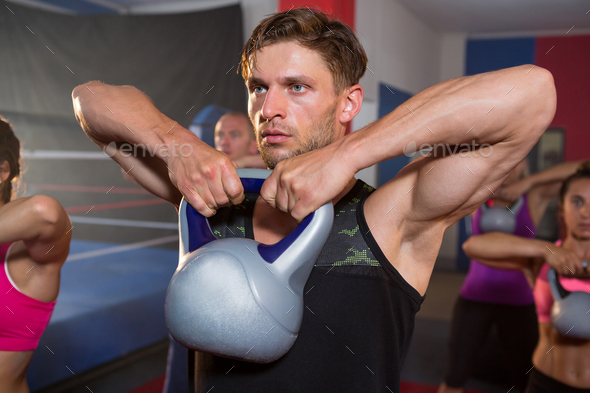 Young man lifting kettle against athletes - Stock Photo - Images