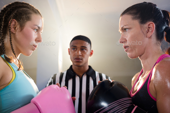 Female boxers looking at each other against referee - Stock Photo - Images