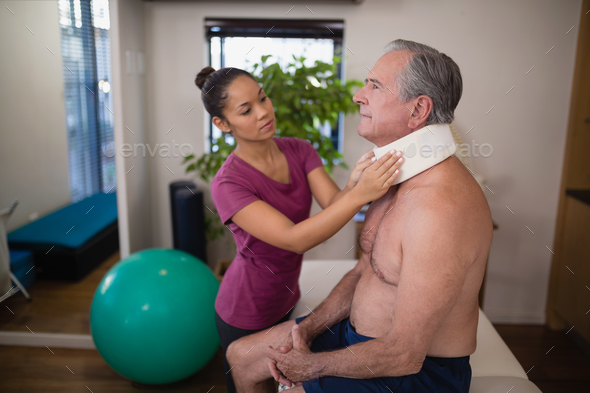 Young female therapist examining neck collar on senior male patient - Stock Photo - Images
