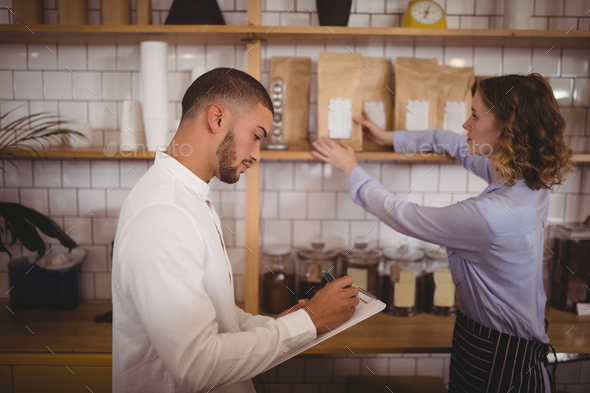 Young male owner writing on clipboard while waitress arranging products - Stock Photo - Images