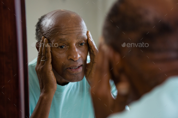 Concerned senior man reflecting on mirror - Stock Photo - Images