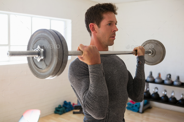 Athelte lifting barbell at gym - Stock Photo - Images