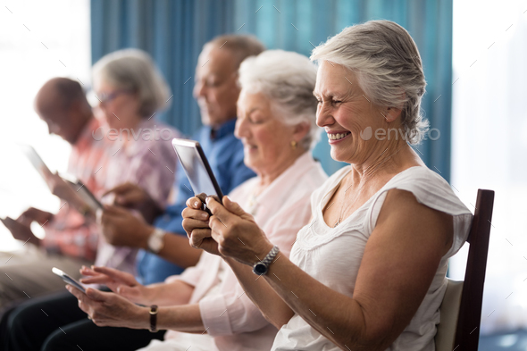 Row of smiling senior people sitting on chairs using digital tablets - Stock Photo - Images
