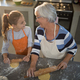 Free Download Grandmother and granddaughter looking at each other while flattening dough Nulled