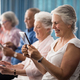 Free Download Row of smiling senior people sitting on chairs using digital tablets Nulled