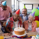 Free Download Happy senior friends by birthday cake at party Nulled