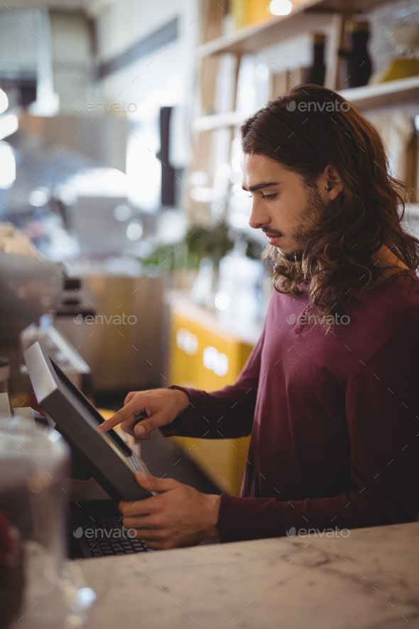 Side view of young waiter with long hair using cash register at counter - Stock Photo - Images