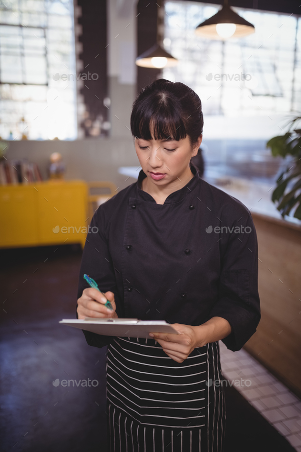 Young attractive female chef writing on clipboard while standing at cafeteria - Stock Photo - Images