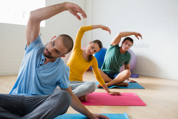 Yoga instructor with students exercising at club - Stock Photo - Images