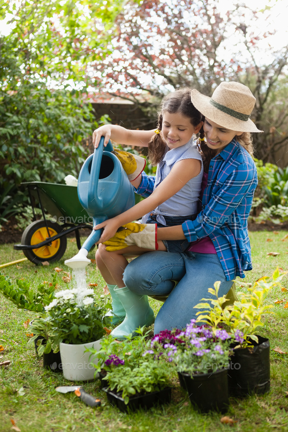 Happy mother teaching daughter to water plants - Stock Photo - Images