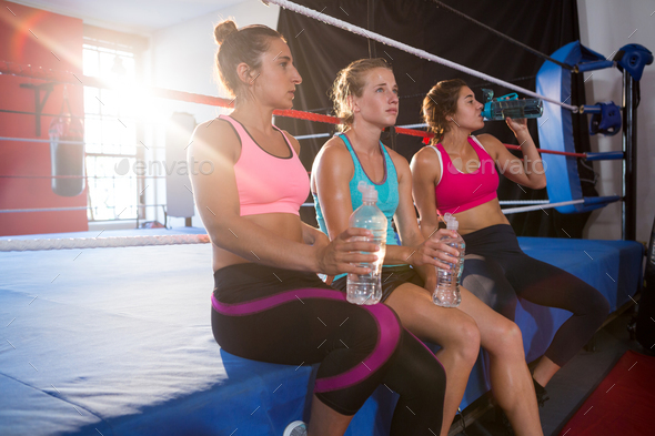 Tired female athletes sitting with water bottles on boxing ring - Stock Photo - Images