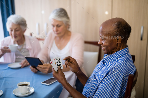 Senior man playing cards with friends while having coffee - Stock Photo - Images