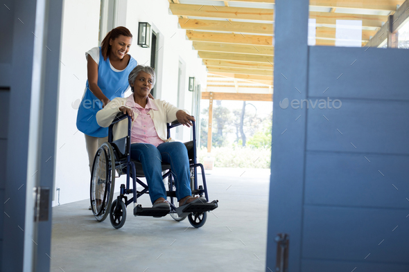 Female doctor pushing happy senior patient in wheelchair - Stock Photo - Images