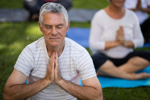 Senior man with eyes closed meditating in prayer position - Stock Photo - Images