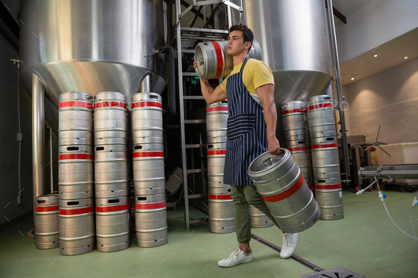 Full length of worker with kegs walking at warehouse - Stock Photo - Images