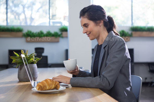 Female executive working at desk while having coffee at table - Stock Photo - Images