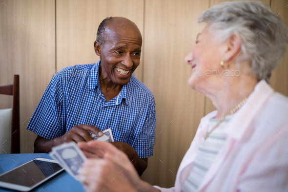 Smiling senior male and female friends playing cards - Stock Photo - Images