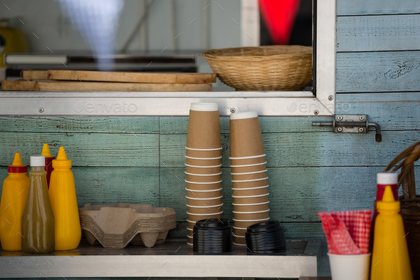 Cups and condiments on table by window - Stock Photo - Images