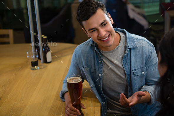 Smiling man talking to friend at bar - Stock Photo - Images