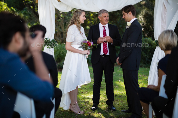 Minister giving speech to bride and groom - Stock Photo - Images