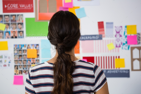 Rear view of businesswoman against sticky notes in office - Stock Photo - Images
