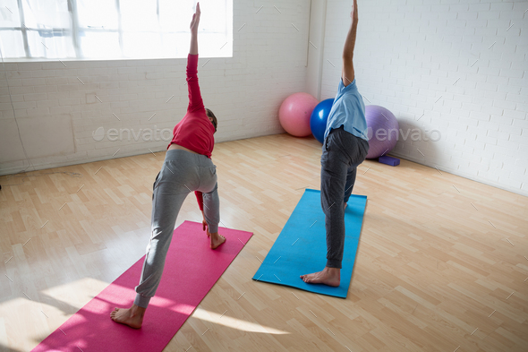 Instructor with female student practicing triangel pose in yoga studio - Stock Photo - Images