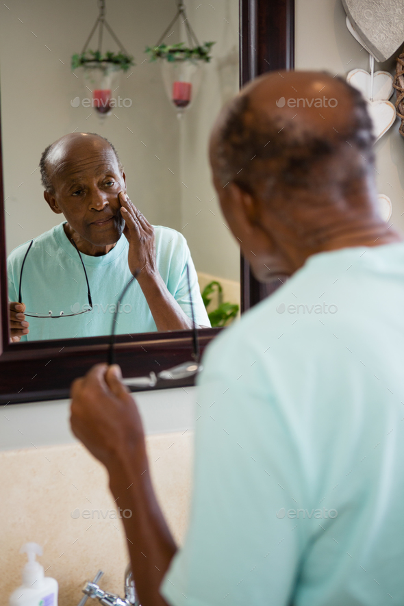 Concerned senior man touching cheek while looking into mirror - Stock Photo - Images