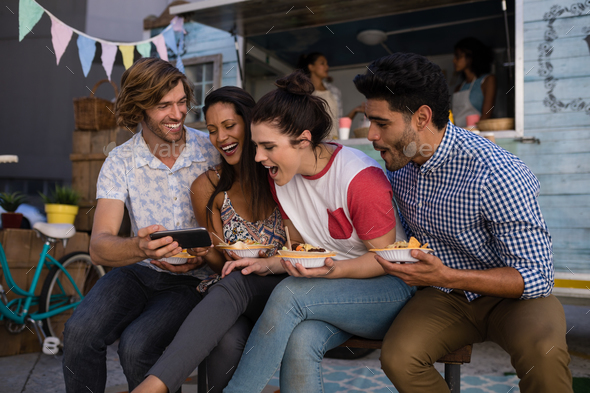 Friends using mobile phone while having snacks - Stock Photo - Images