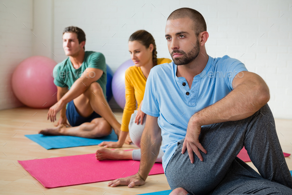 Yoga instructor guiding students in practicing Ardha Matsyendrasana - Stock Photo - Images